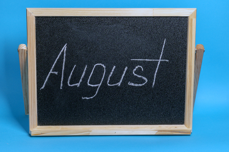 Blackboard with the word chalked august on blue background