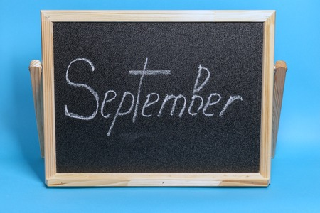 Blackboard with the word chalked september on blue background