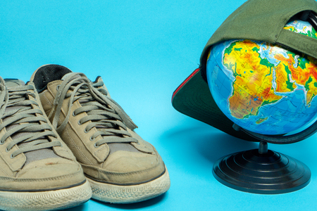 Globe and old worn sneakers in gray on a blue background. Geographical names on the globe in Russian