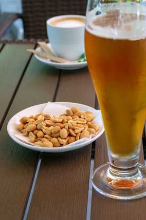 A glass of cold light beer, peanuts in a white saucer and a cup of americano on a wooden table.