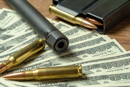 Gewehrlauf, Magazin und Patronen auf Dollar. Konzept für Kriminalität, Auftragsmord, bezahlter Attentäter, Terrorismus, Krieg, globaler Waffenhandel, Waffenverkauf. Illegale Jagd, Wilderei Standard-Bild