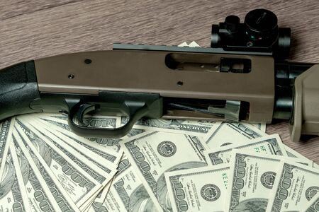 Shotgun on dollars. Concept for crime, global arms trade, weapons sale. Illegal hunting, poaching
