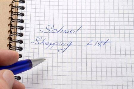 A man writes a blue pen in his notebook. Sign - school shopping list