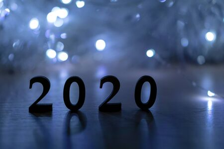 2020 Happy New Year. Silhouette of the number 2020 backlit by a Christmas lights