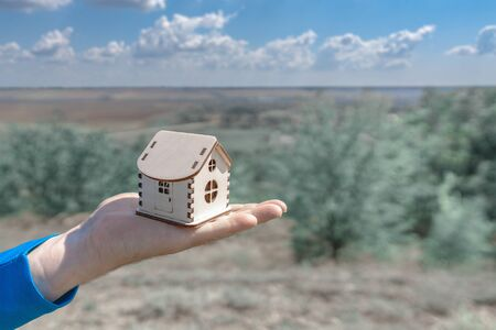 Man holds out a small wooden house in the palm of his hand. Wooden house in the palm of your hand, against the backdrop of a beautiful summer landscape Stock fotó
