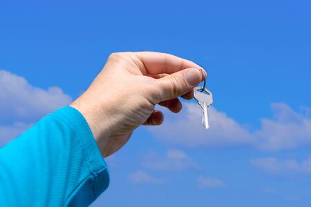 The hand of a white man holds a key on a background of a beautiful summer sky. A man in blue long sleeve holds a key