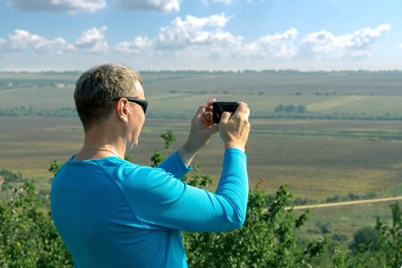 White man photographs the landscape on a smartphone