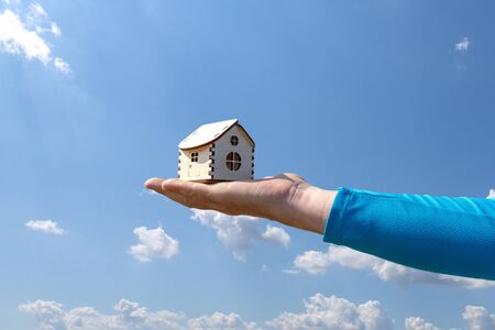 Man holds out a small wooden house in the palm of his hand. Wooden house on the palm of the hand, on a background of cloudy sky Stock fotó