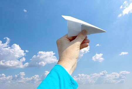 Hand with paper white airplane. A man launches a paper airplane.