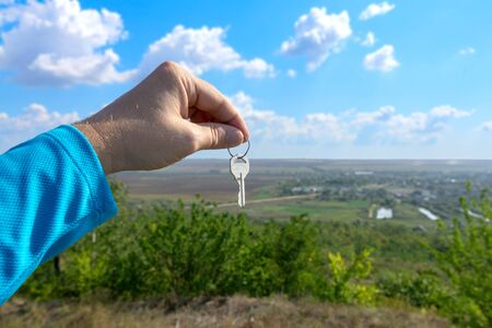 The hand of a white man holds a key on a background of a beautiful summer landscape. A man in a blue long sleeve holds a key