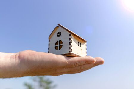 Man holds out a small wooden house in the palm of his hand. Close-up Stock fotó
