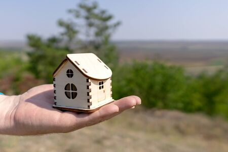 Man holds out a small wooden house in the palm of his hand. Wooden house in the palm of your hand, against the backdrop of a beautiful summer landscape. Close-up