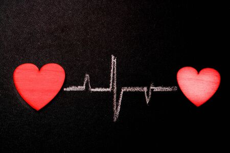 Hearts are connected by a single rhythm. Two hearts on a blackboard with a chalk heart-drawn rhythm