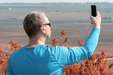 A man in blue longsleeve takes a selfie against the backdrop of a beautiful landscape. Bad cellular signal outside the city, a white man trying to catch a cellular signal
