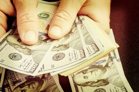 Caucasian hands counting dollar banknotes. Counting or spending USD money banknote, business and finance concept. Toned.