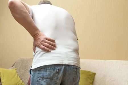 Lower back pain. Man in white shirt holding his back in pain