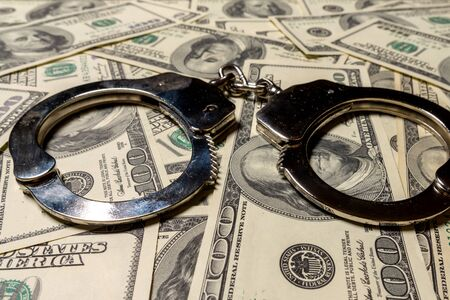 Handcuffs on hundred dollar american banknotes. The concept of corruption, robbery, fraud.