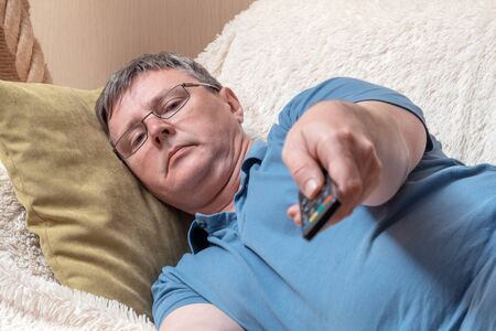 White middle-aged man in a blue t-shirt with a remote control from the TV. A man on a cozy sofa switches television channels