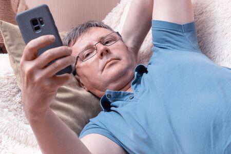 A man with glasses looks at a smartphone while lying in a cozy sofa. Middle-aged businessman checks mail in a smartphone Stock Photo
