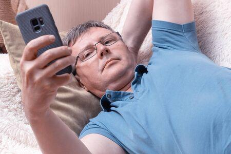Un homme avec des lunettes regarde un smartphone allongé dans un canapé confortable. Un homme d'affaires d'âge moyen vérifie le courrier dans un smartphone Banque d'images