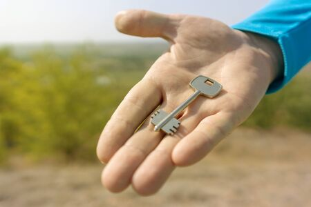 Keys in hand on blur landscape background