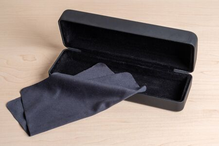 Dark blue case and cloth for cleaning glasses on a light wooden table. Eyeglass storage and care