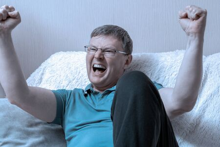 Man sitting on sofa. Excited Man Celebrate Watching Sports On Television