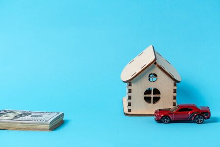 Toy wooden house, red car and hundred dollars banknotes on a blue background. Copy space Stockfoto
