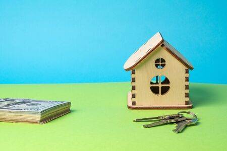 Toy wooden house, keys and hundred dollars banknotes on a blue-green background. Copy space