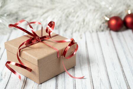 Geschenkbox auf einem Holztisch, dekoriert mit einer Girlande und roten Weihnachtskugeln für das neue Jahr oder XMAS. Post-, Kurier- oder Lieferservice-Konzept. Platz kopieren