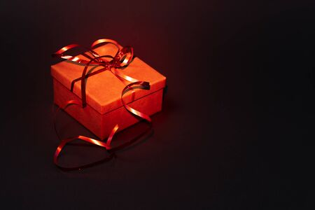 Gift box with a red ribbon on a dark background. Red backlight Stock Photo