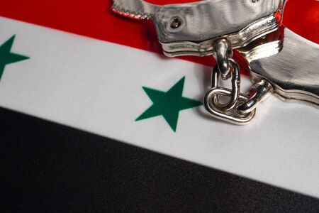 Handcuff on the flag of Syria. Close-up, copy space