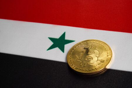 Golden Bitcoin on the flag of Syria. Close-up, copy space.