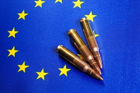 Three rifle cartridges on the flag of European Union. Close-up, copy space