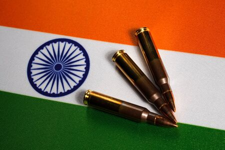 Three rifle cartridges on the flag of India. Close-up, copy space