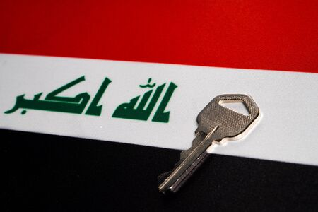 Silver key on the flag of Iraq. Close-up, copy space