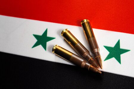 Three rifle cartridges on the flag of Syria. Close-up, copy space