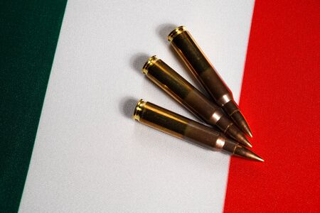 Three rifle cartridges on the flag of Italy. Close-up, copy space.