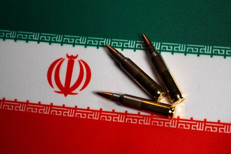Three rifle cartridges on the flag of Iran. Close-up, copy space