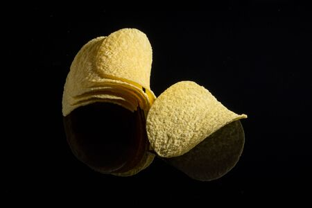 Potato chips on a black glass background. Close-up