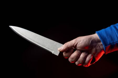 Kitchen knife in a mans hand close-up on a black background Foto de archivo