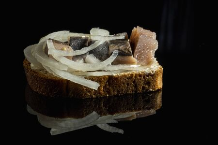 Sandwich with herring and onions. National Russian cuisine. Black glass background. Close up Foto de archivo
