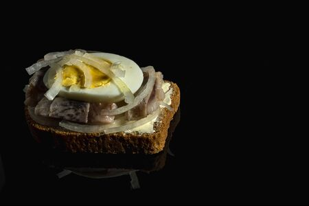 Sandwich with herring, onions and chicken egg. National Russian cuisine. Black glass background Foto de archivo