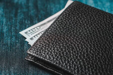 Black genuine leather wallet with banknotes inside, jeans background. Soft focus Foto de archivo