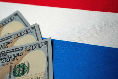 Netherlands national flag and the dollar bills. Business and finance concept, soft focus Foto de archivo