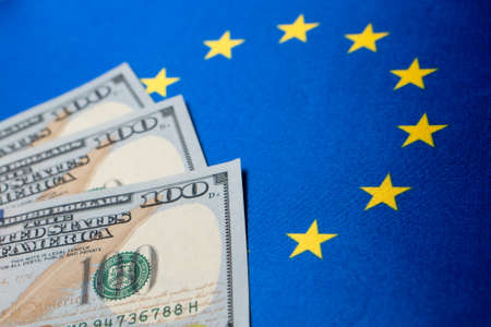 European Union flag and the dollar bills. Business and finance concept, soft focus