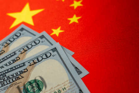 China national flag and the dollar bills. Business and finance concept, soft focus Foto de archivo