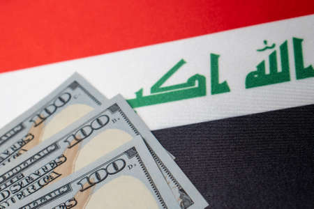 Iraq national flag and the dollar bills. Business and finance concept, soft focus Foto de archivo