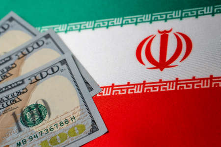 Iran national flag and the dollar bills. Business and finance concept, soft focus