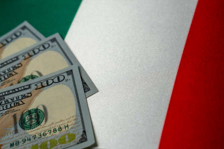 Italy national flag and the dollar bills. Business and finance concept, soft focus
